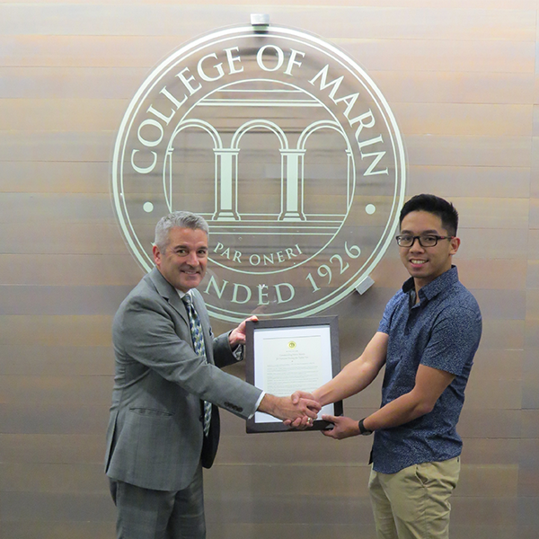 President David Wain Coon presenting student Mario Monte with resolution