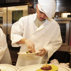 Chef putting food on a plate in a kitchen